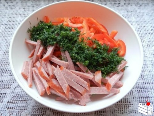 Салат с копченой колбасой и огурцами.